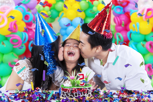 Both parents kissing their child at a birthday party