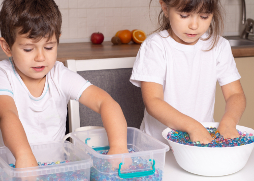 Children on water beads for sensory play