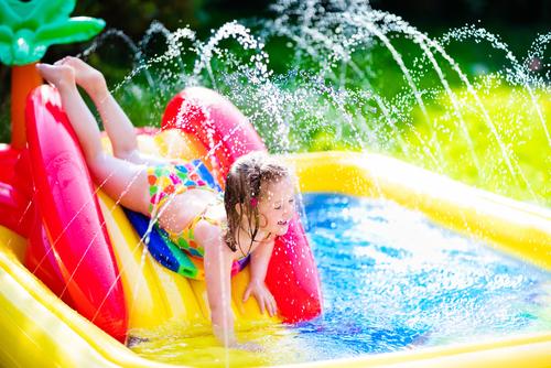 Happy girl enjoying her water slide