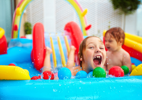 Children on inflatable pool with slide