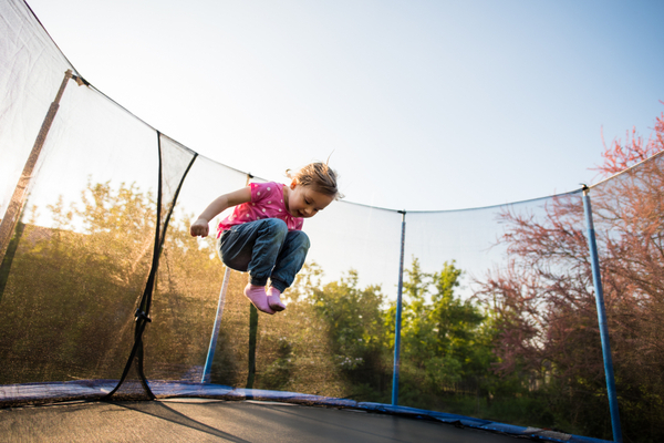 Kid enjoying leisure time as she plays on trampoline
