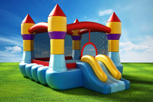 Bounce house standing on green grass. 3D illustration.