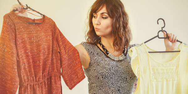 Young woman trying to choose a dress to wear holding up a red and yellow garment on a hanger with a look of indecision as she battles to make up her mind.