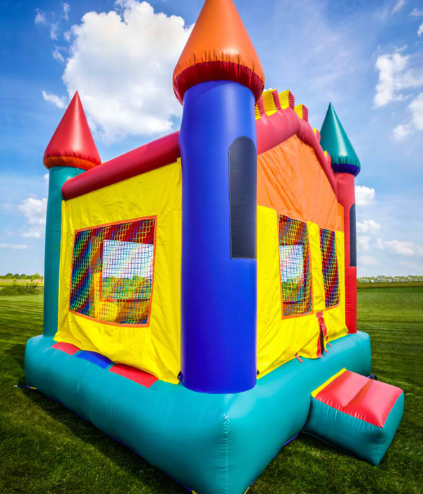 Bounce house inflatable jumpy castle in a large open yard.
