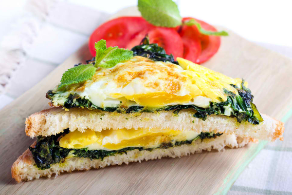 Toasts with roasted spinach and egg on board