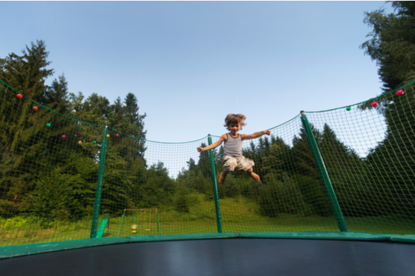 Cute boy enjoys jumping and bouncing on trampoline outdoors.