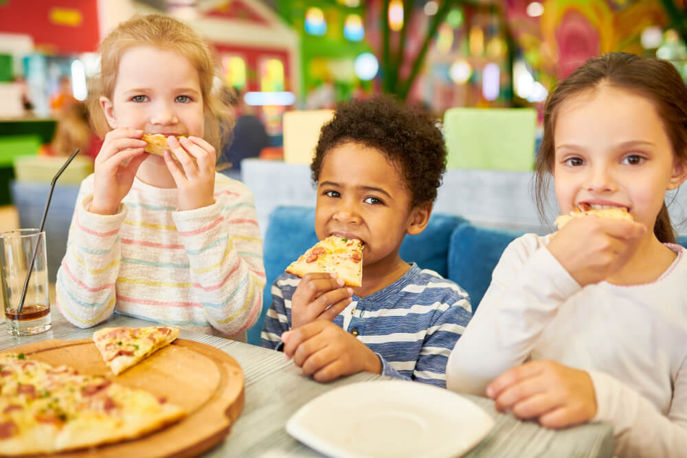 essential party supplies - three kids enjoying pizza on a party