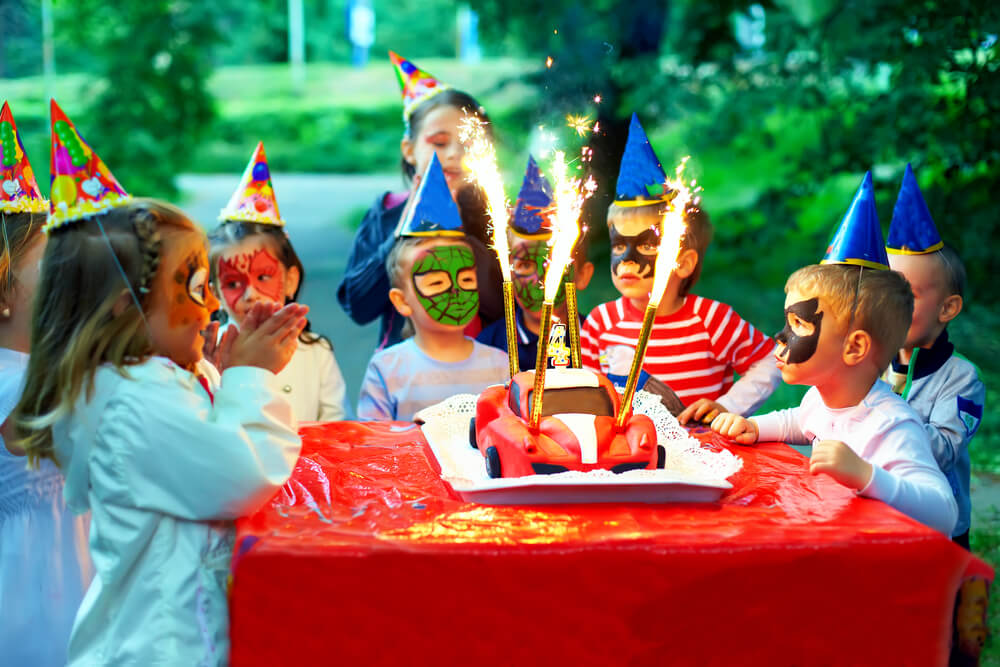 food for parents at a kids' party - kids with masks gather around a birthday cake