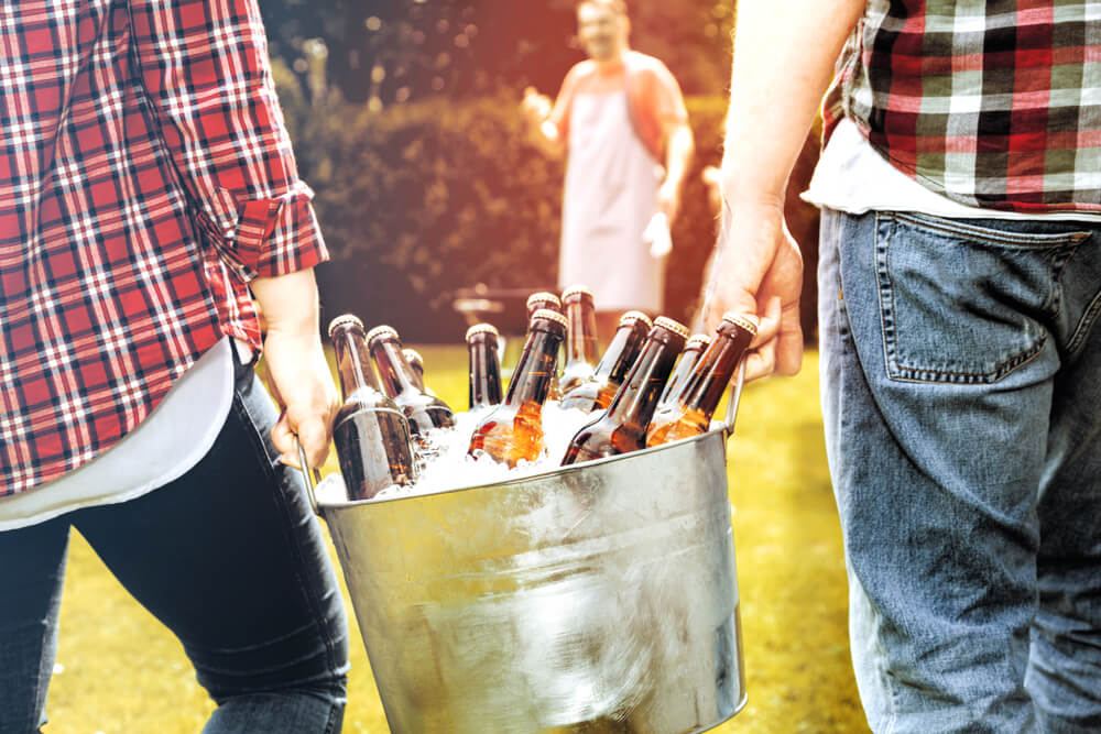food for parents at a kids' party - two men are carrying a bucket of beer