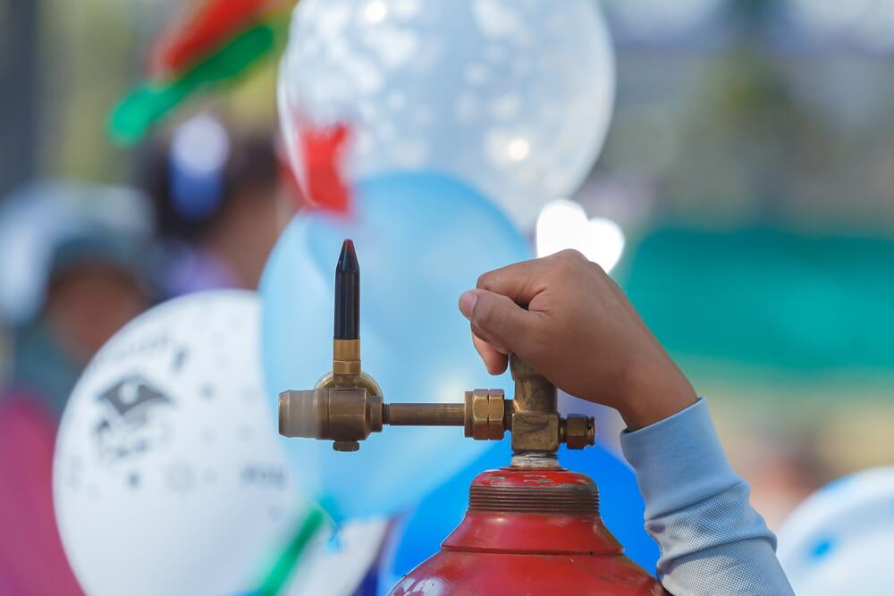 how to blow up a balloon - a hand holding a red helium tank with balloons at the back