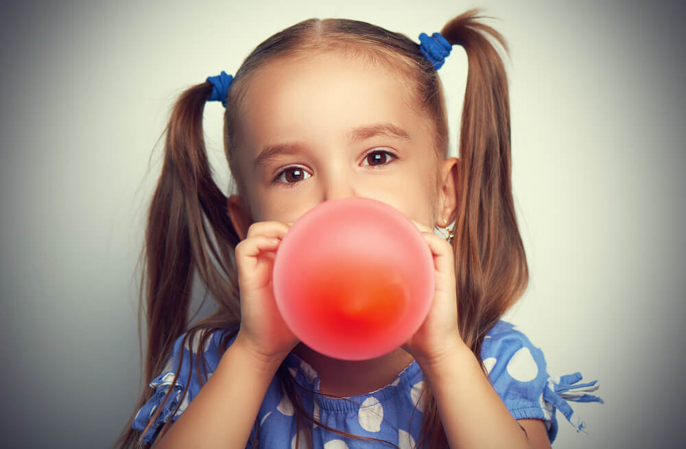 how to blow up a balloon - a little girl in pigtails blowing up a red balloon