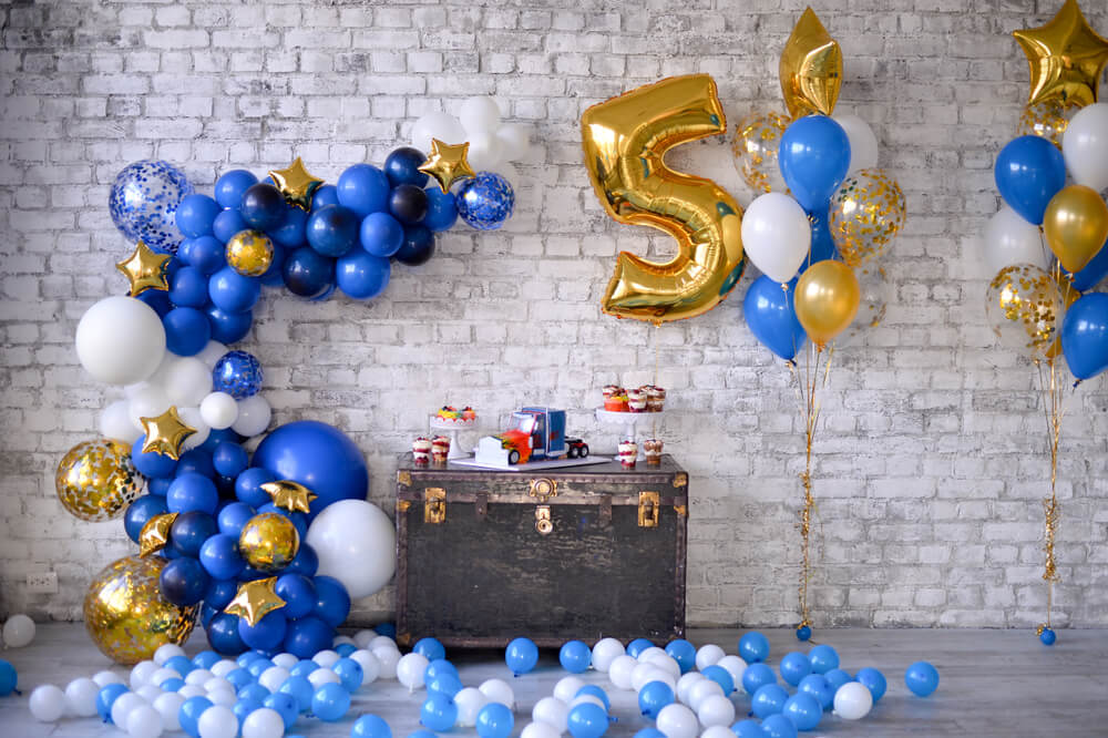how to blow up a balloon - blue, white, and gold balloons decor in a 5-year-old's party