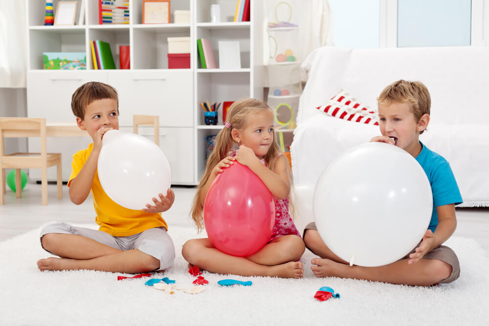 how to blow up a balloon - three kids blowing up white and red balloons at a white living room