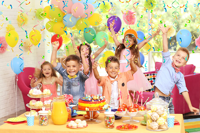 kids enjoying a party with food and balloons