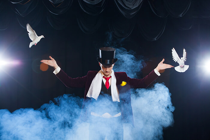 magician doing a trick of two doves - clown or magician