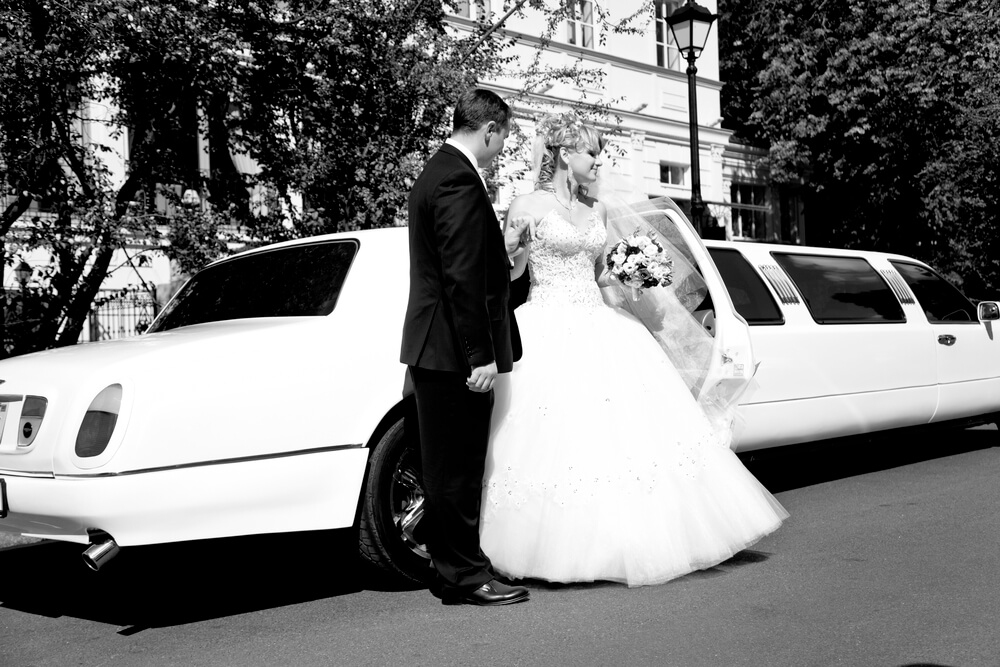 a newly wed couple outside a white stretch limousine